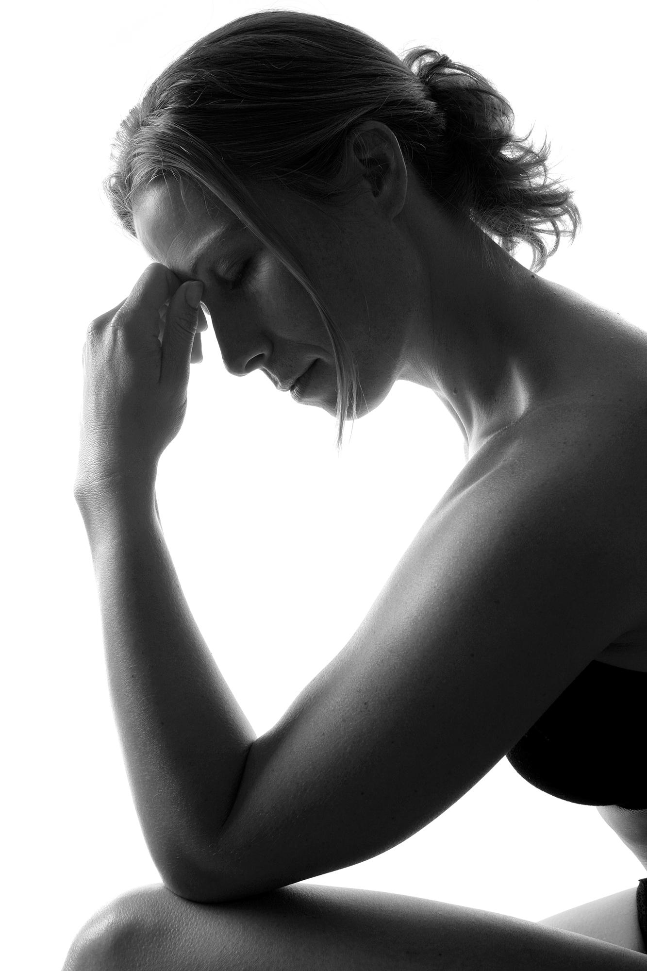 Kvinna med smärta som håller på sin panna