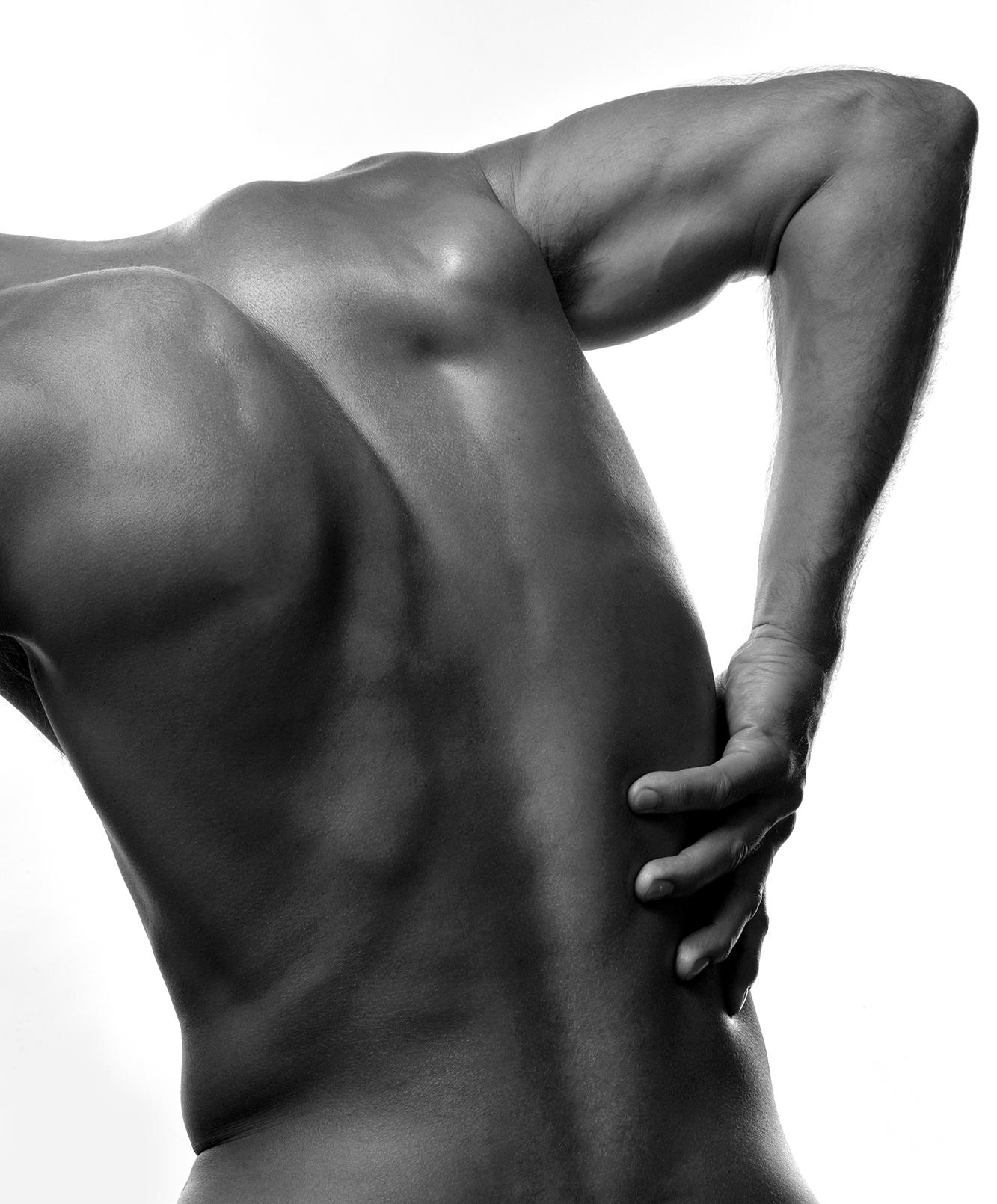 Man med smärta som håller handen på ryggen