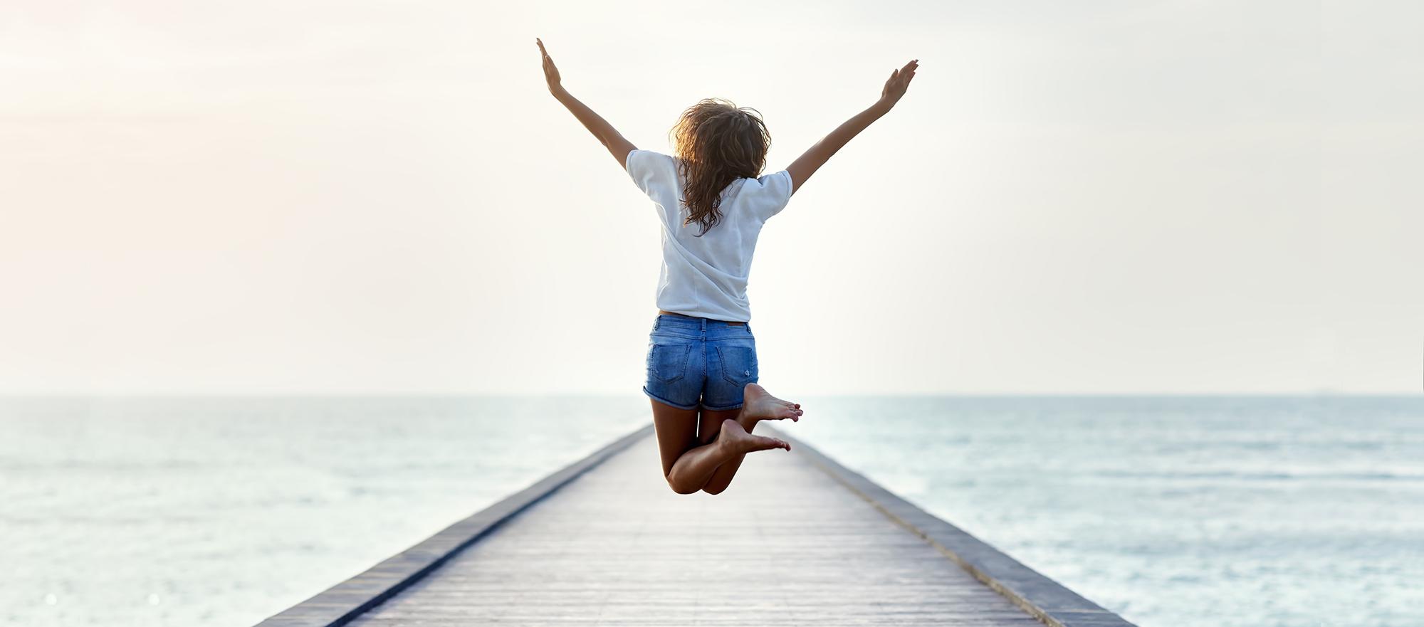 Kvinna som hoppar glädjefyllt på brygga