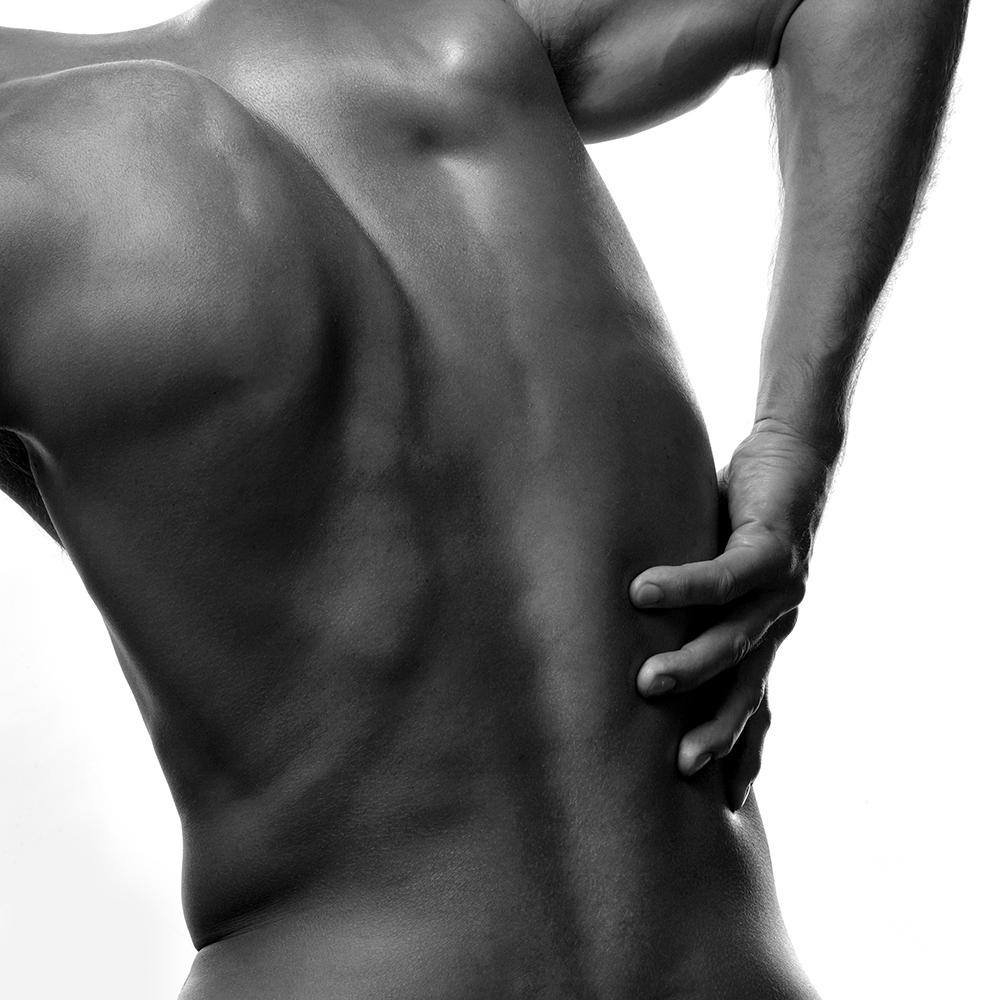 Man med ryggont som håller handen på sin rygg