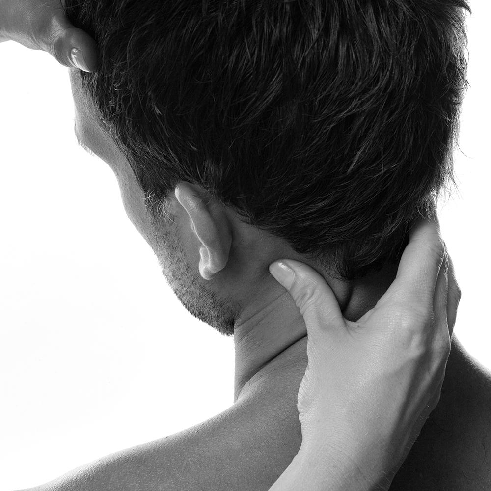Kvinnohänder som håller stabiliserande om en mans nacke och panna